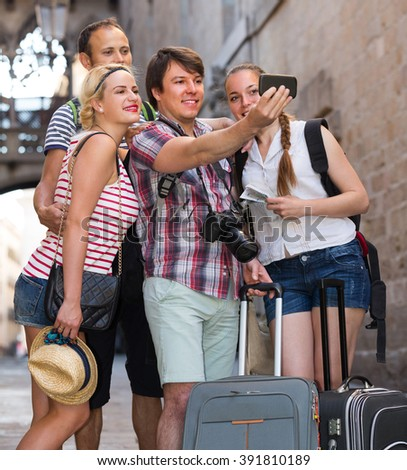 Smiling travelers walking through the city and doing selfie. Selective focus - stock photo