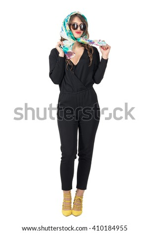 Smiling trendy beauty in jumpsuit wearing sunglasses tying headscarf. Full body length portrait isolated over white studio background.