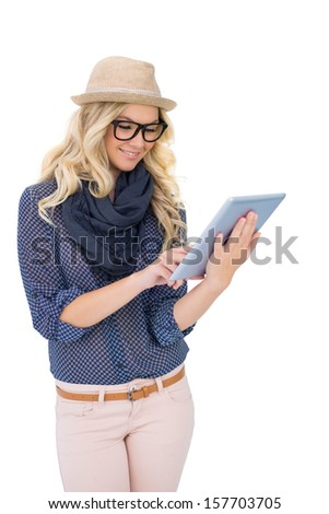 Smiling trendy blonde using tablet computer on white background - stock photo