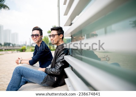 Smiling trendy boys sitting outdoors - stock photo