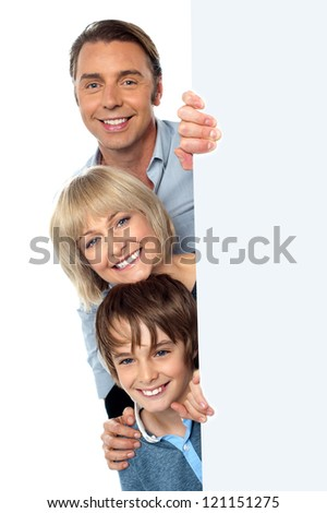 Smiling trio of a father, mother and son peeking from behind an ad space. - stock photo