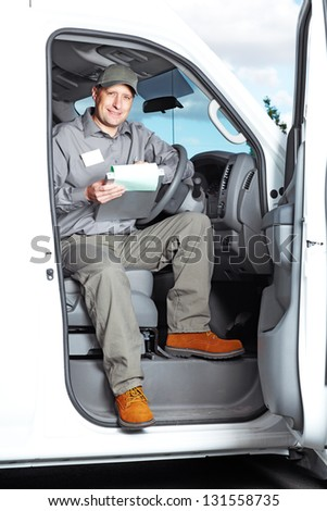 Smiling truck driver in the car. Delivery cargo service. - stock photo