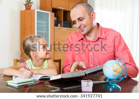 Smiling tutor and cute little girl studying with books at the table in domestic interior