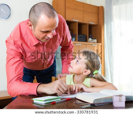 Smiling tutor and little girl doing homework at the table in domestic interior