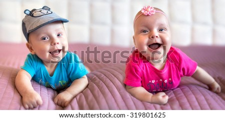 Smiling twin babies lying in bed - stock photo