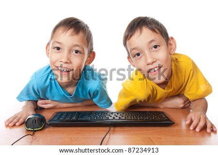 smiling twins with computer mouse and keyboard on their desk isolated on white - stock photo