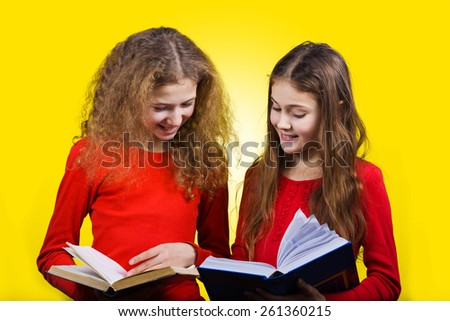 Smiling Two sisters , little schoolgirl reading and holding books in their hands, isolated over yellow background.  - stock photo