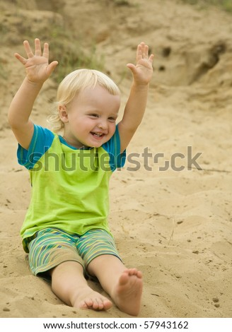 Smiling two-year boy sitting at sand beach