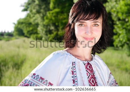 Smiling ukrainian woman outdoors on the summer meadow in traditional shirt - stock photo