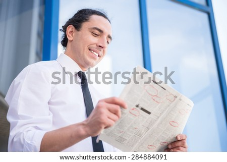 Smiling unemployed man in suit reading newpaper outdoors.