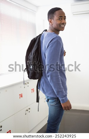 Smiling university student with backpack at the university - stock photo