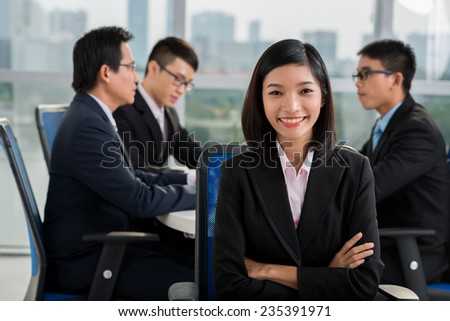 Smiling Vietnamese business lady on the background of her colleagues having a meeting