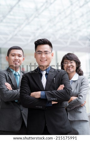 Smiling Vietnamese business team standing with their arms crossed