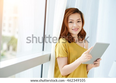 Smiling Vietnamese woman standing at window with tablet computer in her hands
