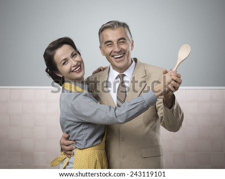 Smiling vintage couple dancing in the kitchen and holding a wooden spoon - stock photo