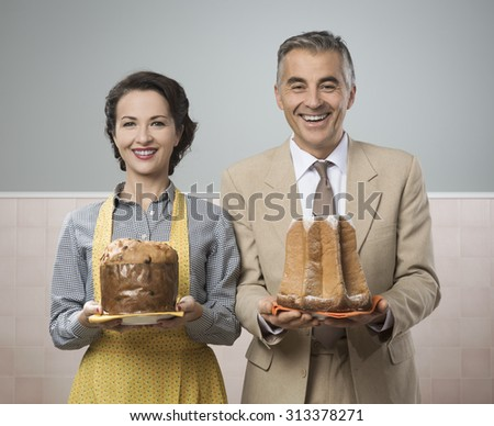 Smiling vintage couple with traditional italian cake panettone and pandoro