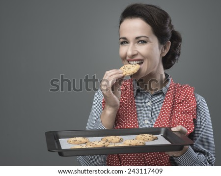 Smiling vintage woman preparing delicious cookies served on a baking tray - stock photo