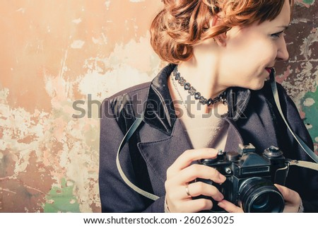 Smiling vintage women with photocamera in her hands, vintage film instagram colors. - stock photo