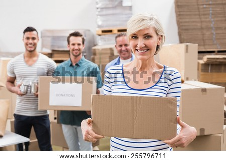 Smiling volunteer showing a poster in a large warehouse - stock photo