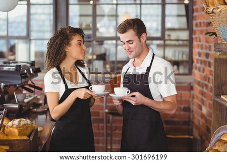 Smiling waiter and waitress holding cup of coffee at coffee shop - stock photo