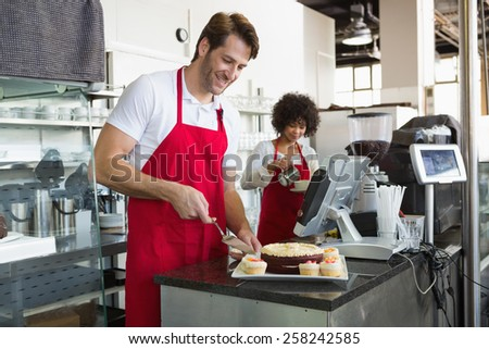 Smiling waiter slicing cake with waitress behind him at the bakery - stock photo