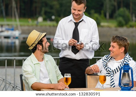 Smiling waiter taking order from men customers outdoor bar - stock photo
