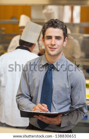 Smiling waiter writing in folder in kitchen