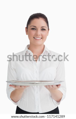 Smiling waitress holding silver tray with two hands - stock photo