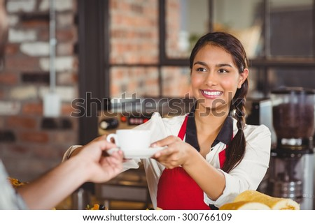 Smiling waitress serving a client at the coffee shop - stock photo