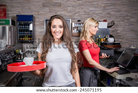 Smiling waitress serving hot coffee in the coffee shop - stock photo