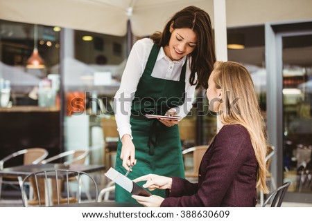 Smiling waitress taking an order in cafe - stock photo