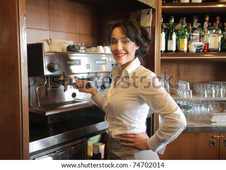 Smiling waitress using a coffee machine in a bar - stock photo