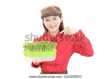 Smiling waitress with plants.