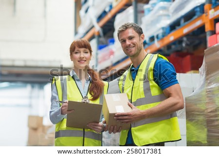 Smiling warehouse manager and delivery man in warehouse - stock photo