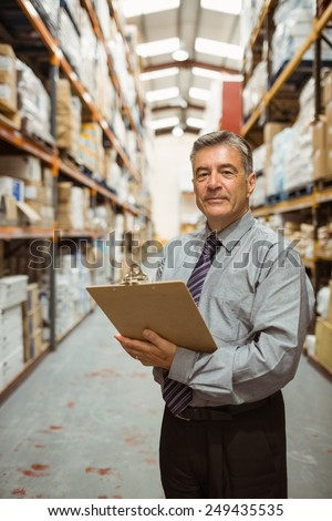 Smiling warehouse manager holding a clipboard in a large warehouse