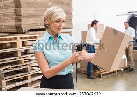 Smiling warehouse manager scanning package in warehouse - stock photo