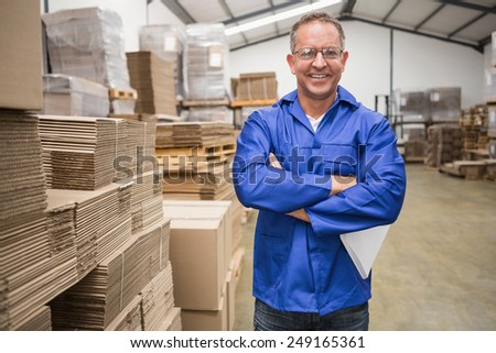 Smiling warehouse manager standing with arms crossed in a large warehouse - stock photo