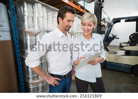 Smiling warehouse managers with clipboard in a large warehouse - stock photo