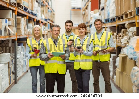 Smiling warehouse team looking at camera in a large warehouse - stock photo