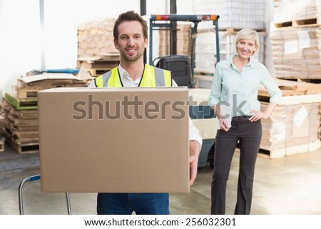 Smiling warehouse worker carrying box in warehouse - stock photo