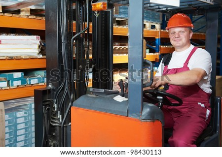 Smiling Warehouse worker distributing goods in a storehouse with forklift truck loader stacker - stock photo