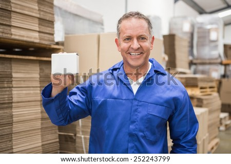 Smiling warehouse worker holding small box in a large warehouse - stock photo