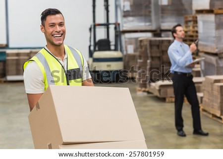 Smiling warehouse worker moving boxes on trolley in a large warehouse - stock photo