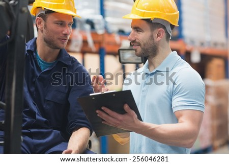 Smiling warehouse workers talking together in warehouse - stock photo