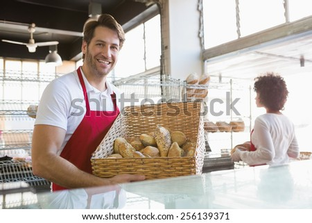 Smiling water carrying basket of bread at the bakery - stock photo
