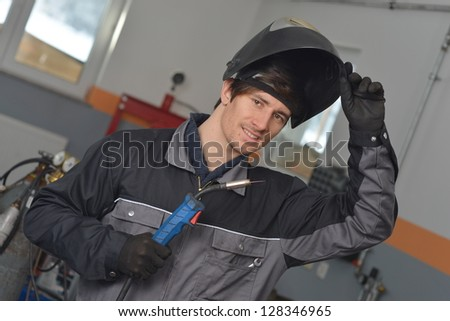 Smiling welder in gray workwear and helmet at work place - stock photo