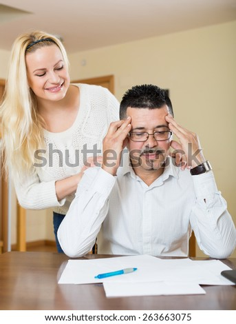 Smiling wife consoling anxious husband thinking of a debts  - stock photo