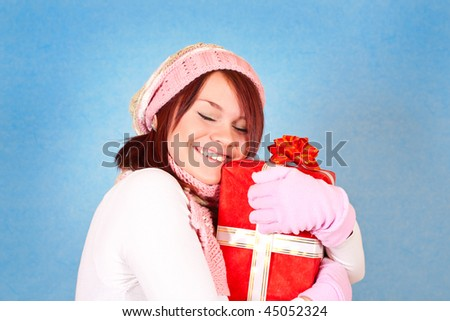 smiling winter girl hugging the red present