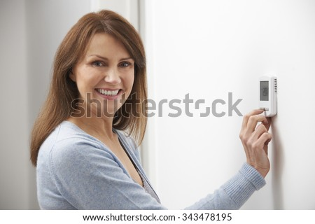 Smiling Woman Adjusting Thermostat On Home Heating System - stock photo