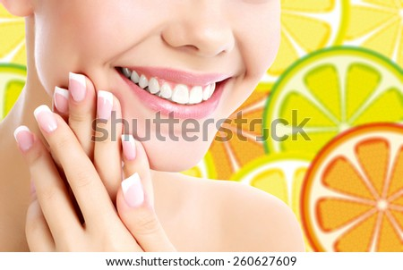 Smiling woman against a background with the orange slices - stock photo